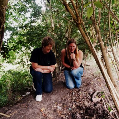 Laura and Pauline looking at a badget sett entrance - wildlife gardening