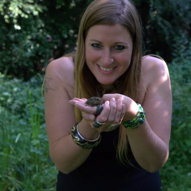 Laura with a toad in a wildlife garden